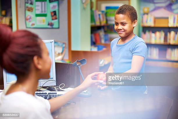 Librarian giving an appple to boy