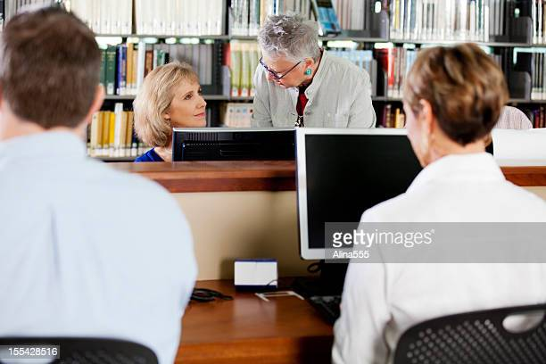 Librarian helping awoman working on computer