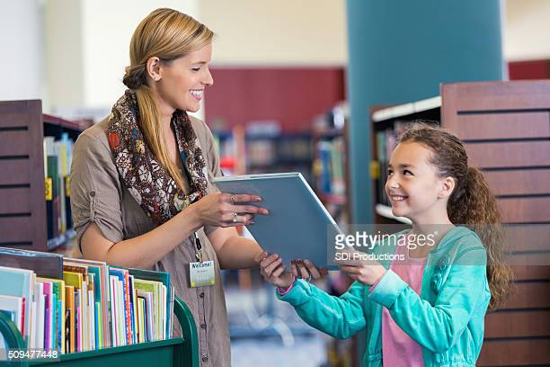 Librarian helping elementary age little girl with book selection