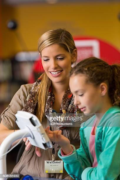 Bibliothécaire aidant Élève du primaire avec tablette numérique de la technologie