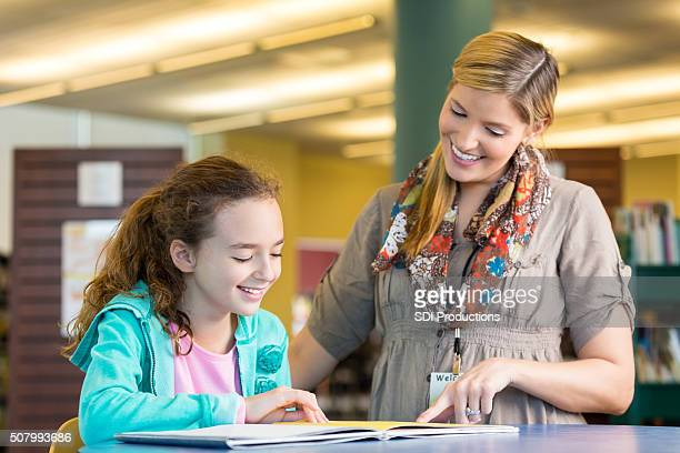 Librarian helping little girl read childrens book in public library