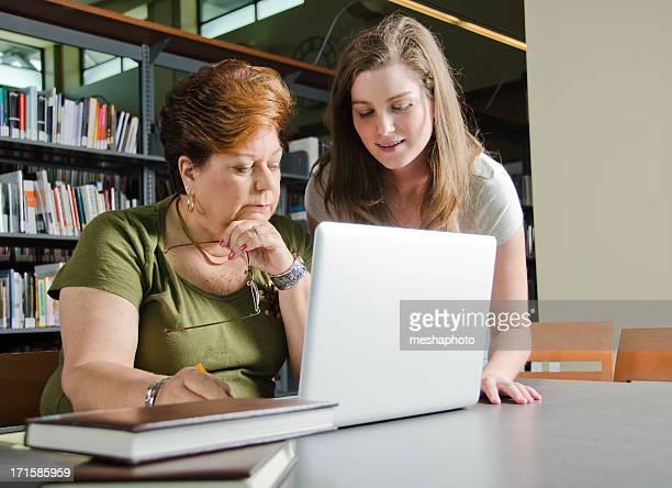 Bibliotecario aiutando donna anziana con Computer portatile