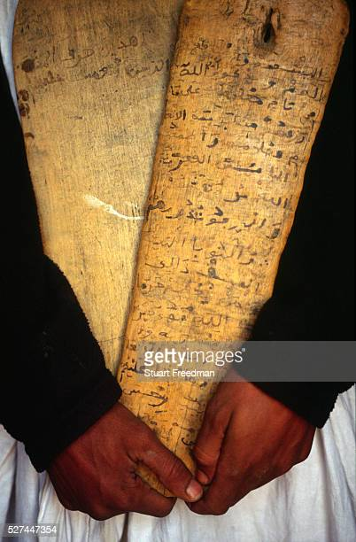 A librarian in Chingetti Mauritania holding a 'lah' or wooden tablet on which is inscribed verses of the Koran Chinguetti was a 'ksar' or medieval...