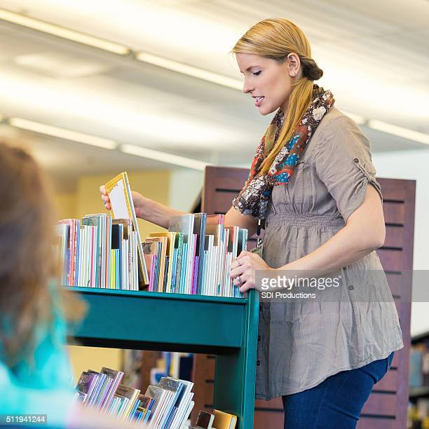 Librarian in elementary school sorting books on book cart