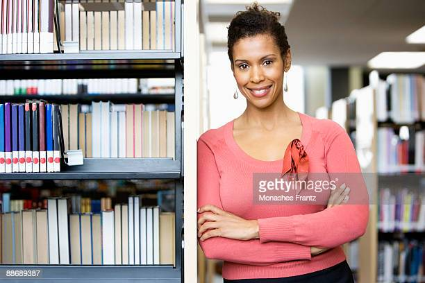 Librarian leaning on shelves in library