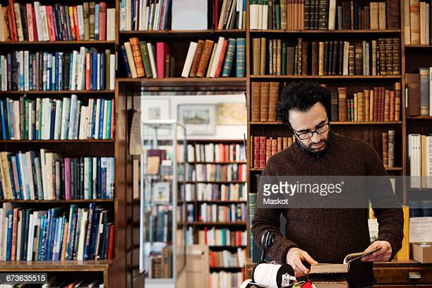 Librarian reading book while standing against shelves