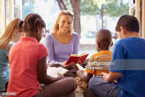 librarian reads aloud to a group of children - día fotografías e imágenes de stock