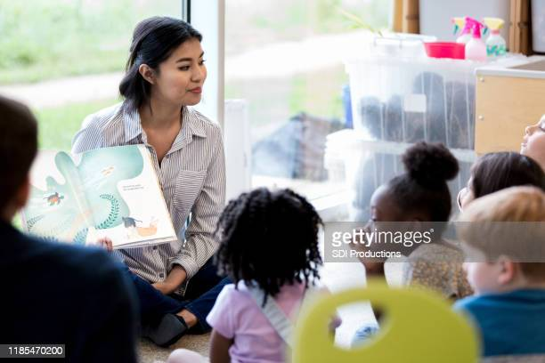 librarian reads children a book during story time - elementary age stock pictures, royalty-free photos & images