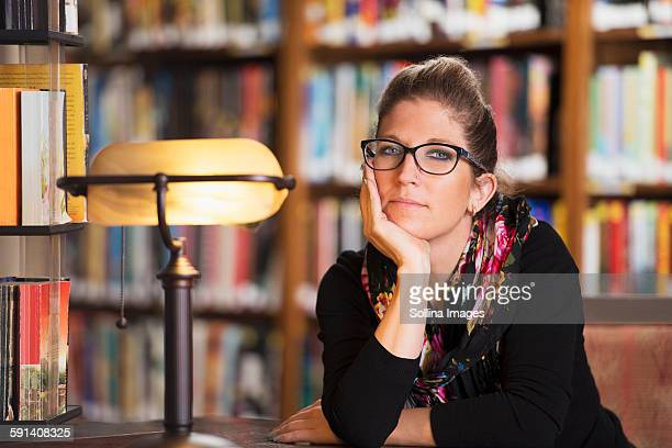 Librarian sitting at desk in library