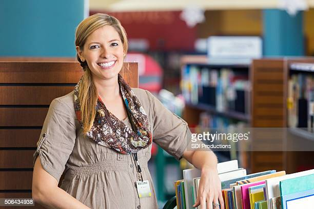 Librarian smiling near book cart in modern public library
