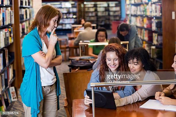 bibliotecário diga aos estudantes a ser silenciosos na escola, biblioteca - silêncio - fotografias e filmes do acervo