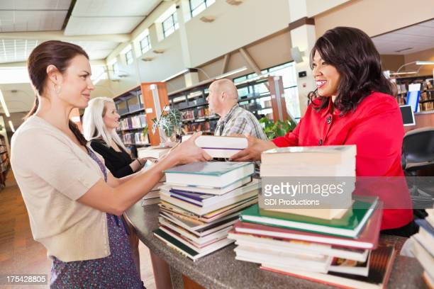 Librarians helping people check out books in the library