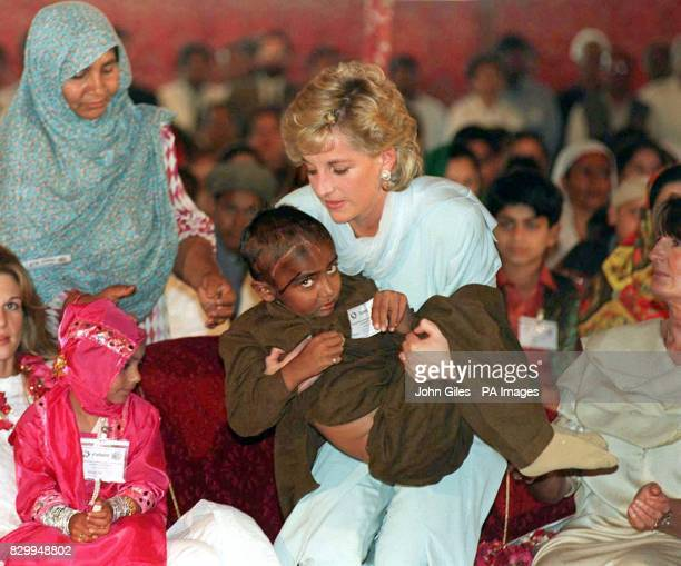 Library file dated 22296 of Diana Princess of Wales cradling a sick child at a reception held at the Shaukat Khanum Cancer Hospital during her visit...