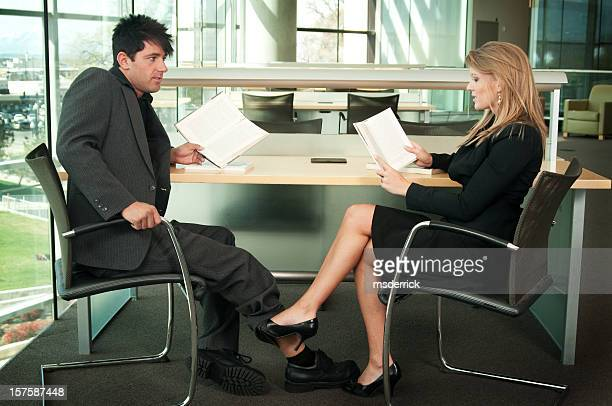 library flirting - playing footsie stock photos and pictures