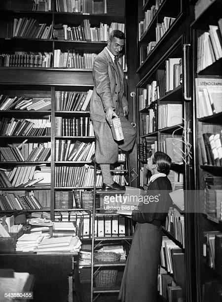 Library Man of the ladder is giving a woman a book from the high bookshelf Photographer Curt Ullmann Published by 'Sieben Tage' 43/1936 Vintage...