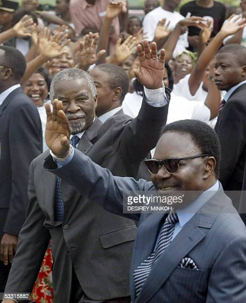 South African President Thabo Mbeki and his Gabonese counterpart Omar Bongo Ondimba wave to the crowds following Mbeki's arrival at the airport in...