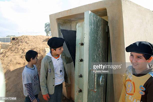 BENGHAZI Libya Boys look at the entrance to a dungeon at a military facility in Benghazi in northeastern Libya which is effectively controlled by...