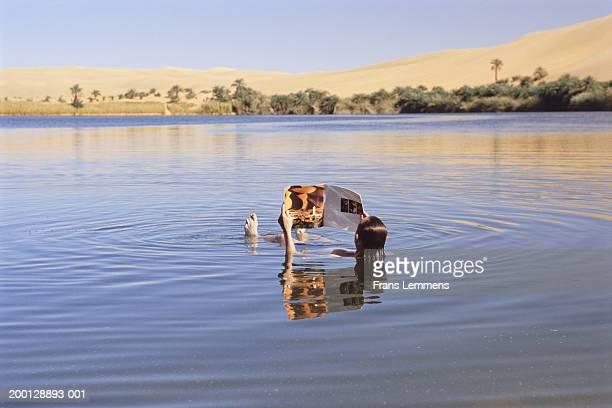 Libya, Fezzan, Ubari, man reading magazine in Lake Gabraoun, rear view