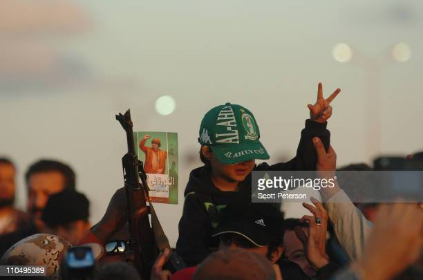 Libyan boy and a gun are held up with a booklet of Libyan leader Muammar Gaddafi as regime loyalists prepare graves for 24 Libyan servicemen March...