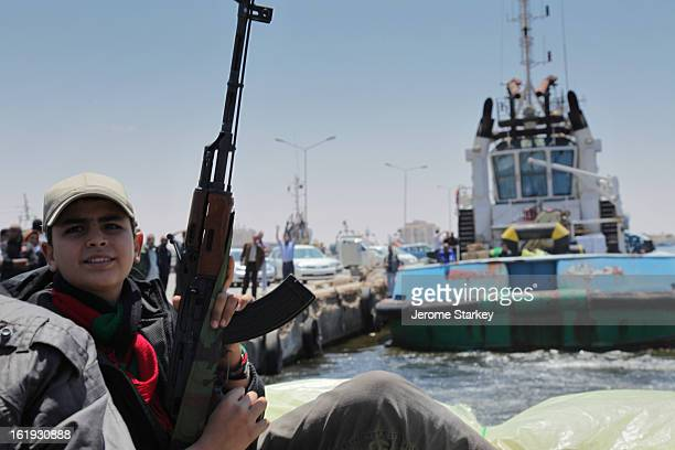 Libyan boy clutches an AK47, as he waits on board a tug boat laden with weapons and ammunition for a passage across the bay of Sirte, to the besieged...