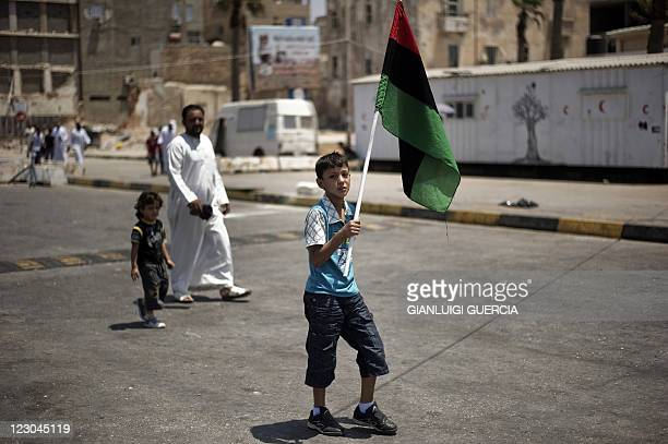 A Libyan boy holds the flag of the former Libyan monarchy that was adopted by the revolution as he arrives at Freedome Square after the first Friday...
