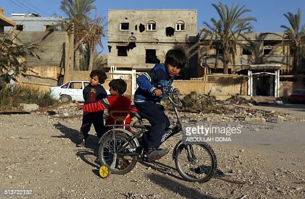 A Libyan boy rides his bicycle in front of destroyed building on March 4 2016 in Laithi district a central area that was recently reseized by forces...