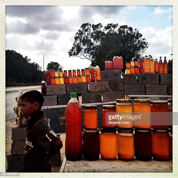 Libyan boy sells fresh honey along the road to Tripoli on July 17 2012 in Homes Libya