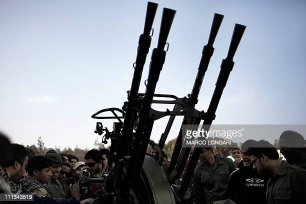 Libyan civilians gather around an antiaircraft gun as they register in the opposition forces in Benghazi on March 1 2011 Libyan rebels said they have...