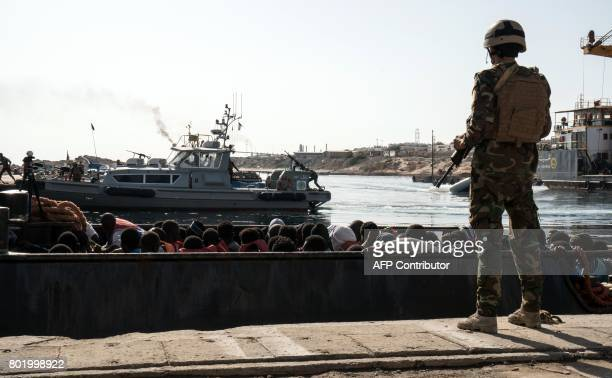 Libyan coast guardsman watches over as illegal immigrants arrive to land in a dinghy during the rescue of 147 people who attempted to reach Europe...