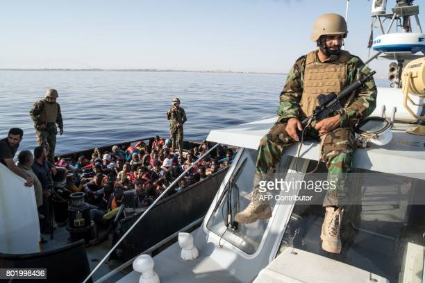 A Libyan coast guardsman watches over during an operation to rescue illegal immigrants who attempted to reach Europe off the coastal town of Zawiyah...