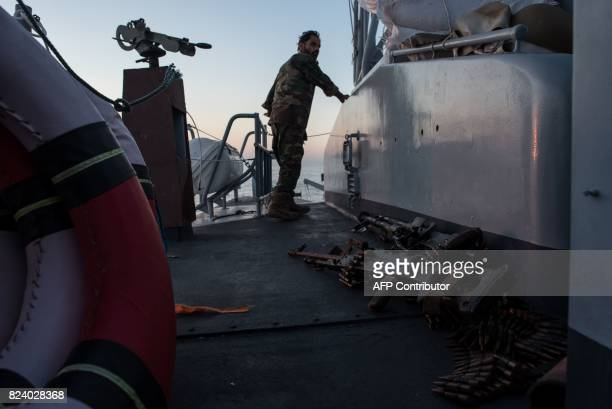 A Libyan coastguard looks on as he patrols the area at sea between Sabratha and Zawiyah on July 28 2017 / AFP PHOTO / TAHA JAWASHI