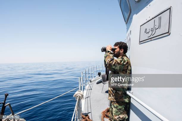 A Libyan coastguard uses binoculars as he patrols the area at sea between Sabratha and Zawiyah on July 28 2017 / AFP PHOTO / TAHA JAWASHI