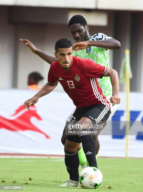Libyan defender Mohammad Abdellas takes possession of the ball from Nigerian Olaolu Aina during the African Cup of Nations qualification match...