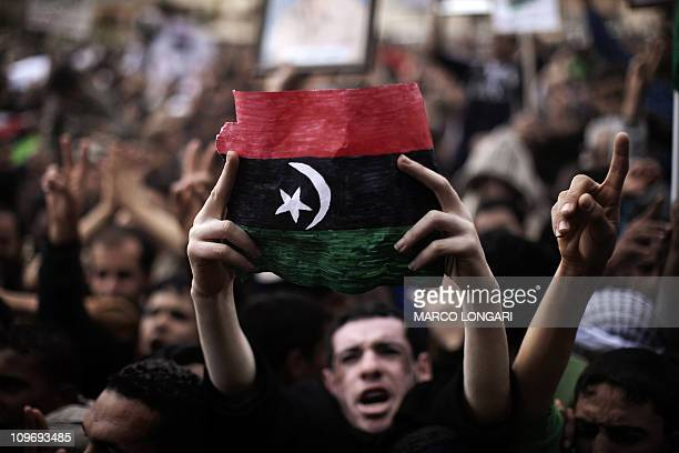 A Libyan demonstrator holds his country's old flag during a protest in the eastern city of Tobruk on February 25 2011 Libya was on edge as forces...