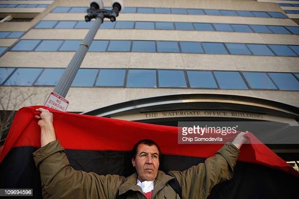 Libyan demonstrators display the preGaddafi Libyan flag while standing outside the offices of the Libyan ambassador to the United States March 1 2011...