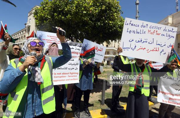 Libyan demonstrators hold signs against what they call foreign intervention in Libya during a protest outside the municipality of Tripoli on April 16...