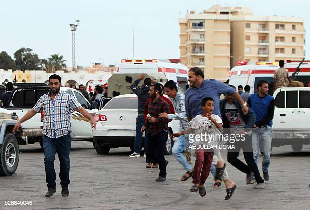 Libyan demonstrators run for cover from shelling during a protest in the eastern coastal city of Benghazi calling for military forces to recapture...