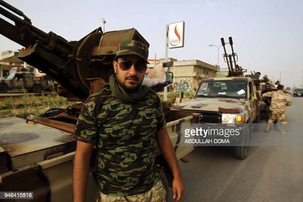 A Libyan fighter loyal to Libyan strongman Khalifa Haftar gathers near the coastal city of Derna on April 14 as they await the start of military...