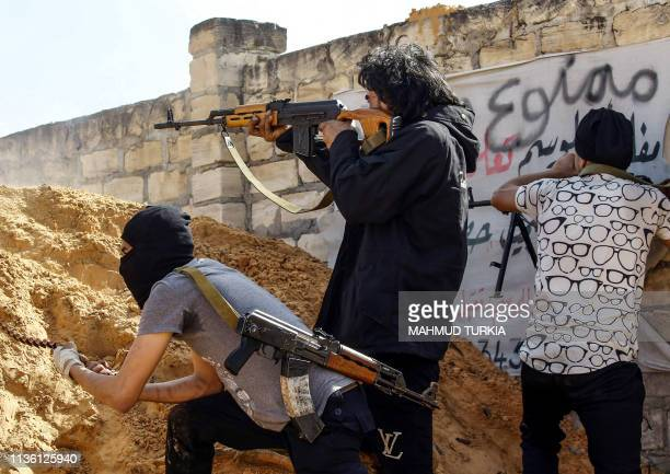 A Libyan fighter loyal to the Government of National Accord fires an assault rifle while taking cover behind a dirt barrier during clashes with...