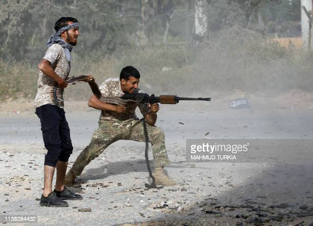 Libyan fighter loyal to the Government of National Accord fires his rifle as a fellow fighter holds a bullet chain during clashes with forces loyal...