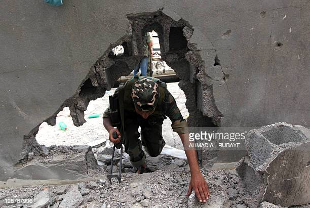 A Libyan fighter loyal to the National Transitional Council crawls through a hole in a wall as they fight against troops loyal to former leader...
