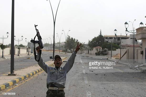 A Libyan fighter loyal to the National Transitional Council flashes the Vsign for victory during fighting against troops loyal to former leader...