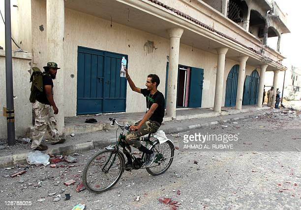 A Libyan fighter loyal to the National Transitional Council rides a bike during a lull in fighting against troops loyal to former leader Moamer...