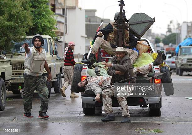 Libyan fighters evacuate the body of a comrade killed during battles with forces loyal to Moamer Kadhafi in the city of Sirte on October 10 2011 in a...