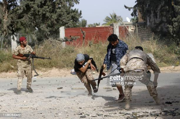TOPSHOT Libyan fighters loyal to the Government of National Accord run as they fire their guns during clashes with forces loyal to strongman Khalifa...