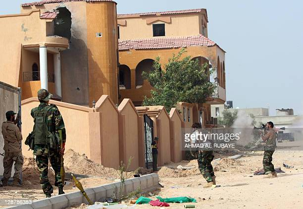 Libyan fighters loyal to the National Transitional Council fight along a street against troops loyal to former leader Moamer Kadhafi in the town of...