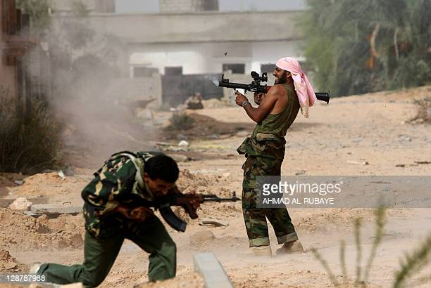 Libyan fighters loyal to the National Transitional Council fire and take cover as they fight against troops loyal to former leader Moamer Kadhafi in...