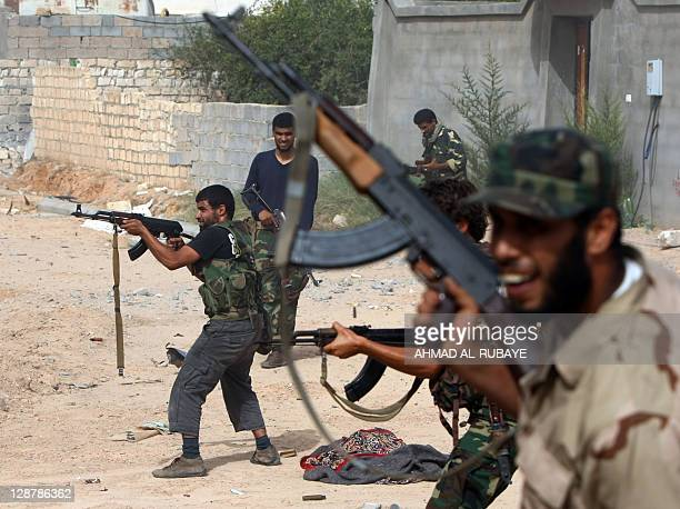 Libyan fighters loyal to the National Transitional Council fire their weapons during fighting against troops loyal to former leader Moamer Kadhafi in...