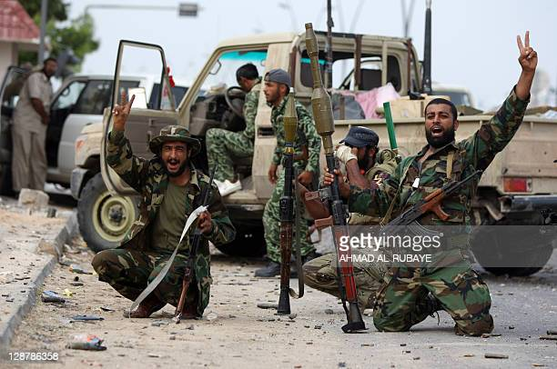 Libyan fighters loyal to the National Transitional Council flash the Vsign for victory as they fight against troops loyal to former leader Moamer...