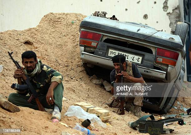 Libyan fighters loyal to the National Transitional Council take cover behind a sand mound during fighting against troops loyal to former leader...